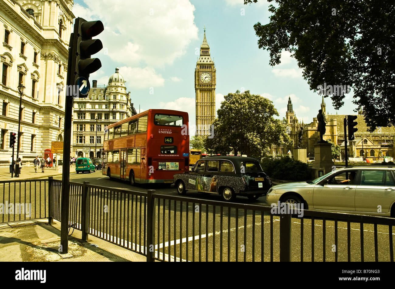 A view of the street with black taxis, red double decker buses and Big Ben in the background London UK - Stock Image