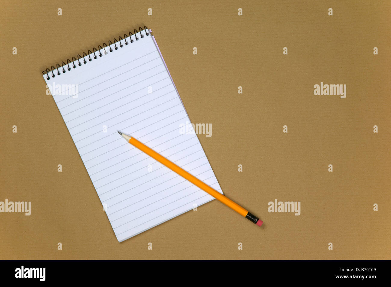 Blank reporters notebook and pencil on a brown paper background - Stock Image
