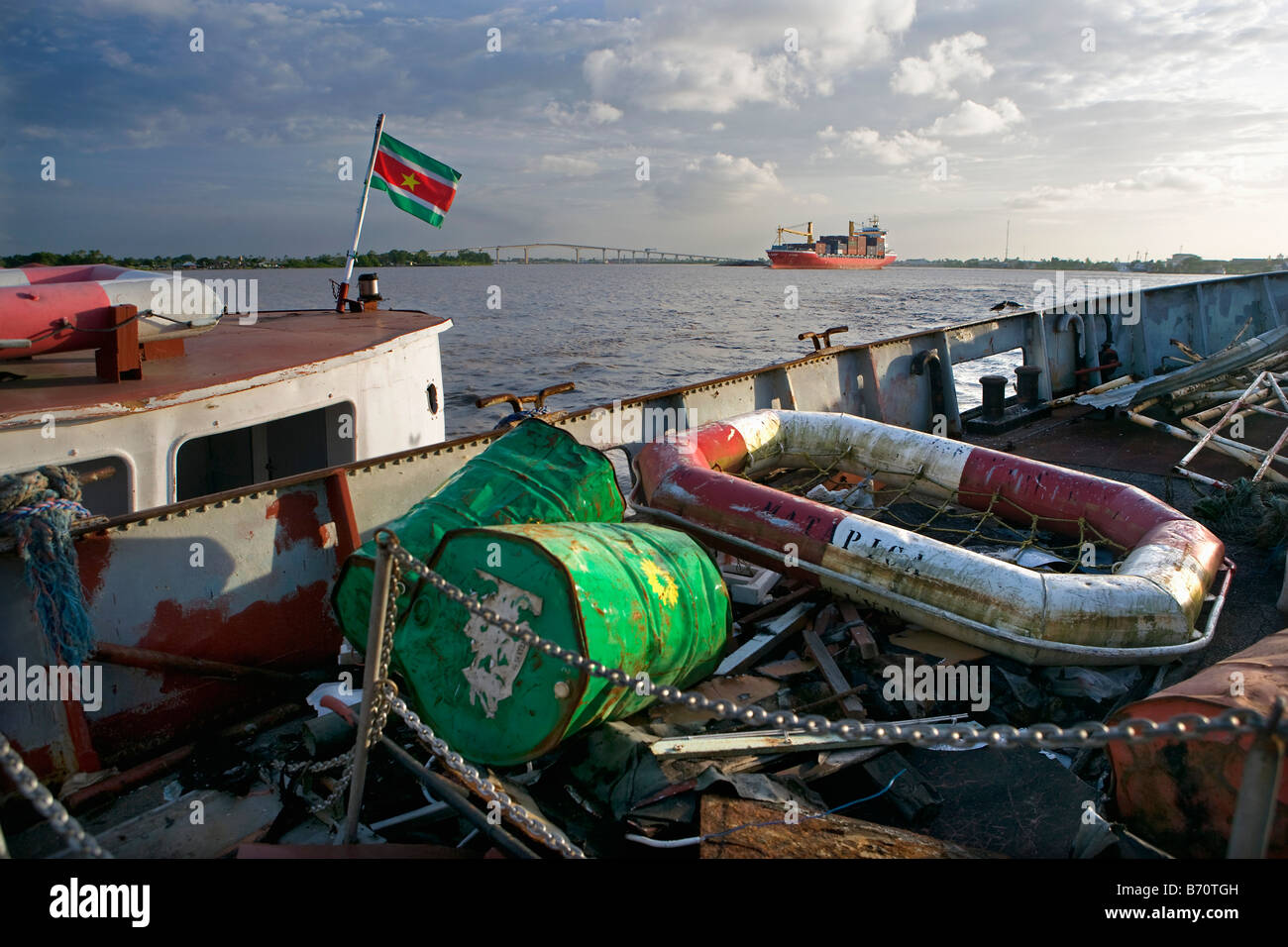 Suriname, Paramaribo. View from deserted ship in Suriname river, in background container ship and Wijdenbosch bridge. Stock Photo