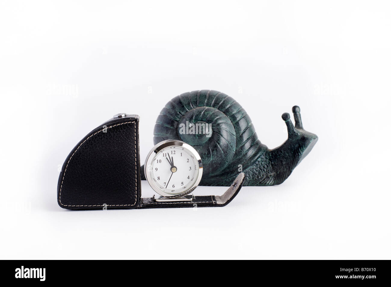 similarly shaped clock and carved snail side by side - Stock Image