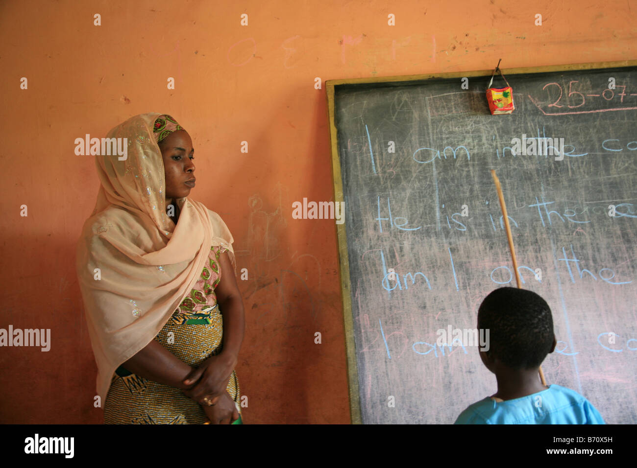 A young boy is learning English at the islamic school in Sunyani Ghana praying at the mosque In Ghana coranic schools - Stock Image