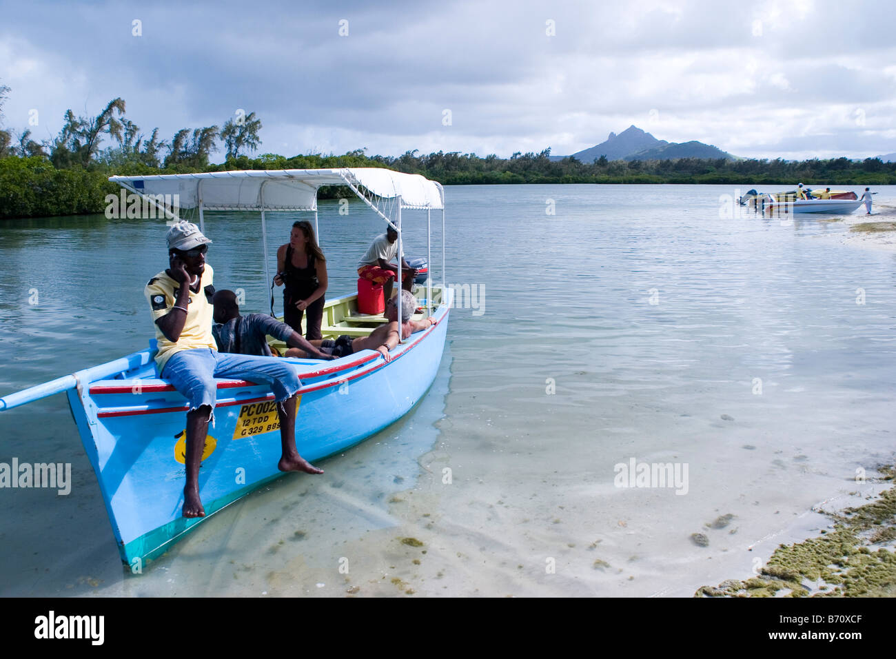 A local guide takes a break for a phone call on his boat on the island of Mauritius. - Stock Image