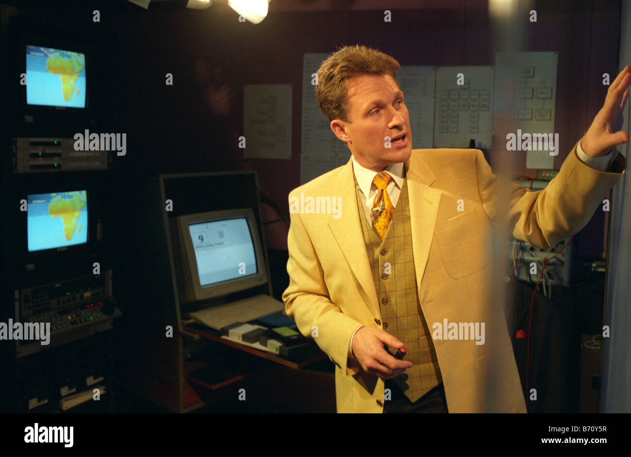 Richard Edgar presenting the weather forecast at BBC Television centre weather studio for the BBC World Service - Stock Image