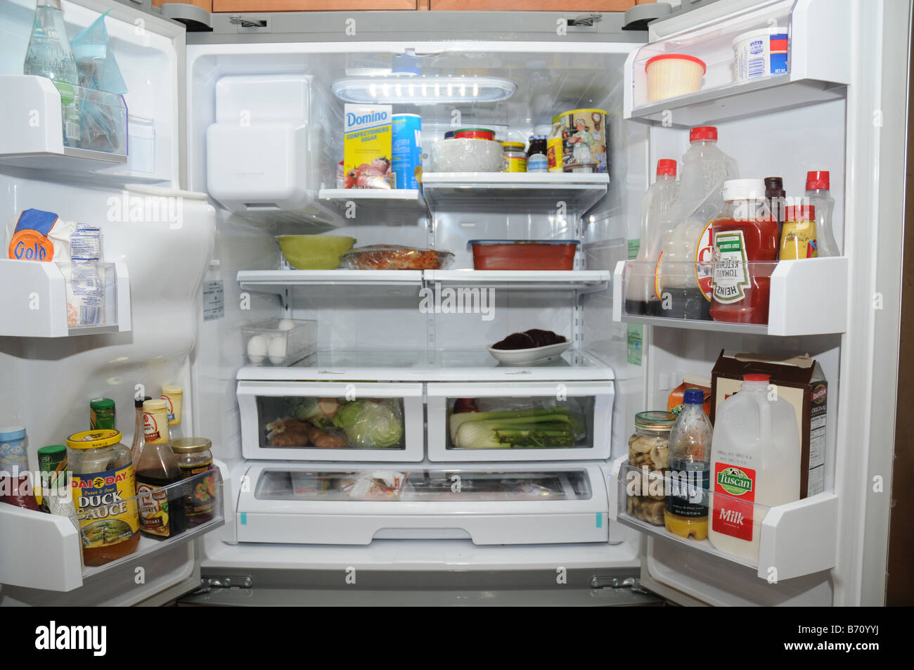 Open Double Door Refrigerator Exposing The Contents Inside
