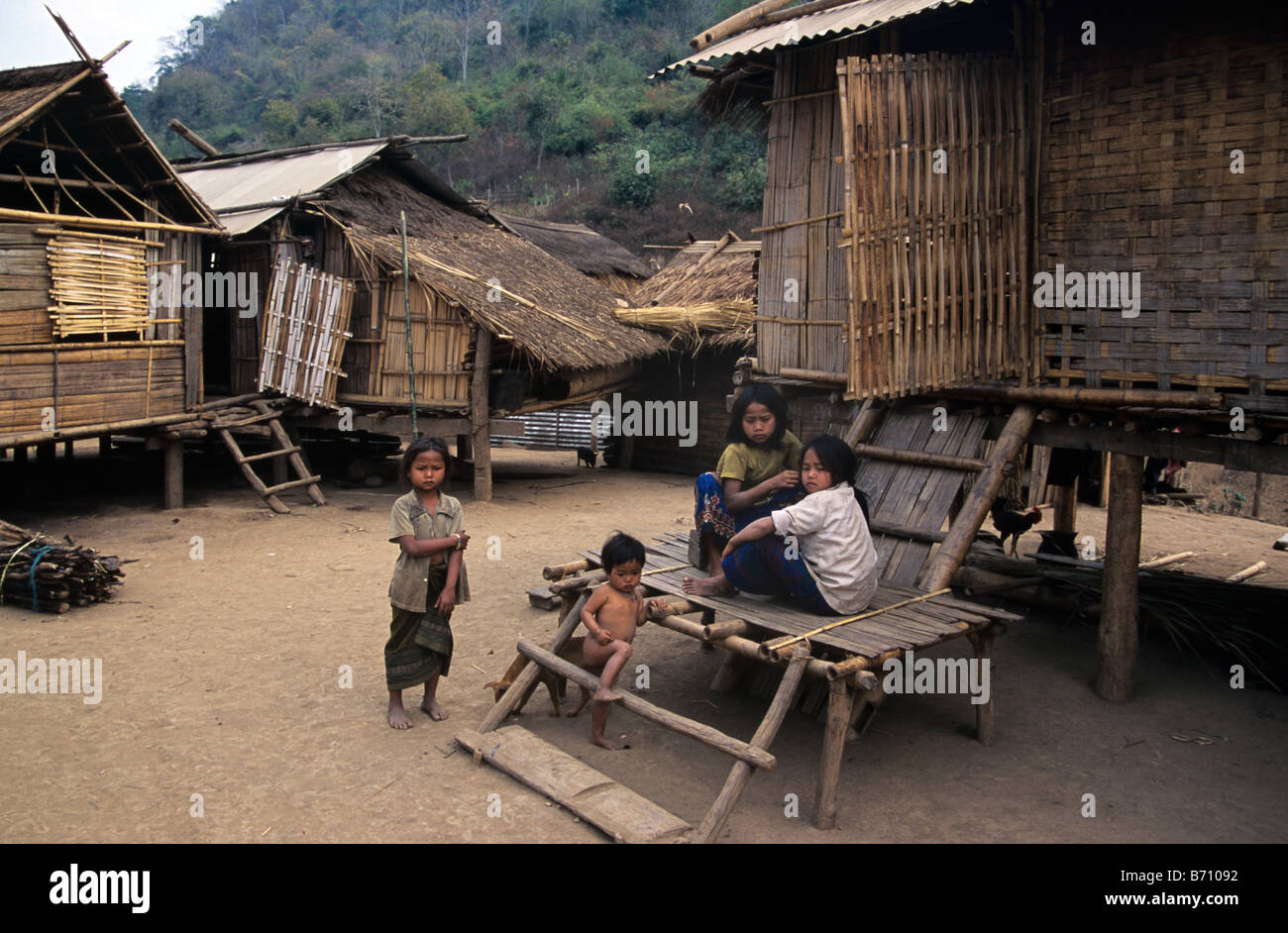 Hmong Children or Family Outside their Traditional Bamboo & Grass Houses in the Upland Lao Village of Khamu, - Stock Image