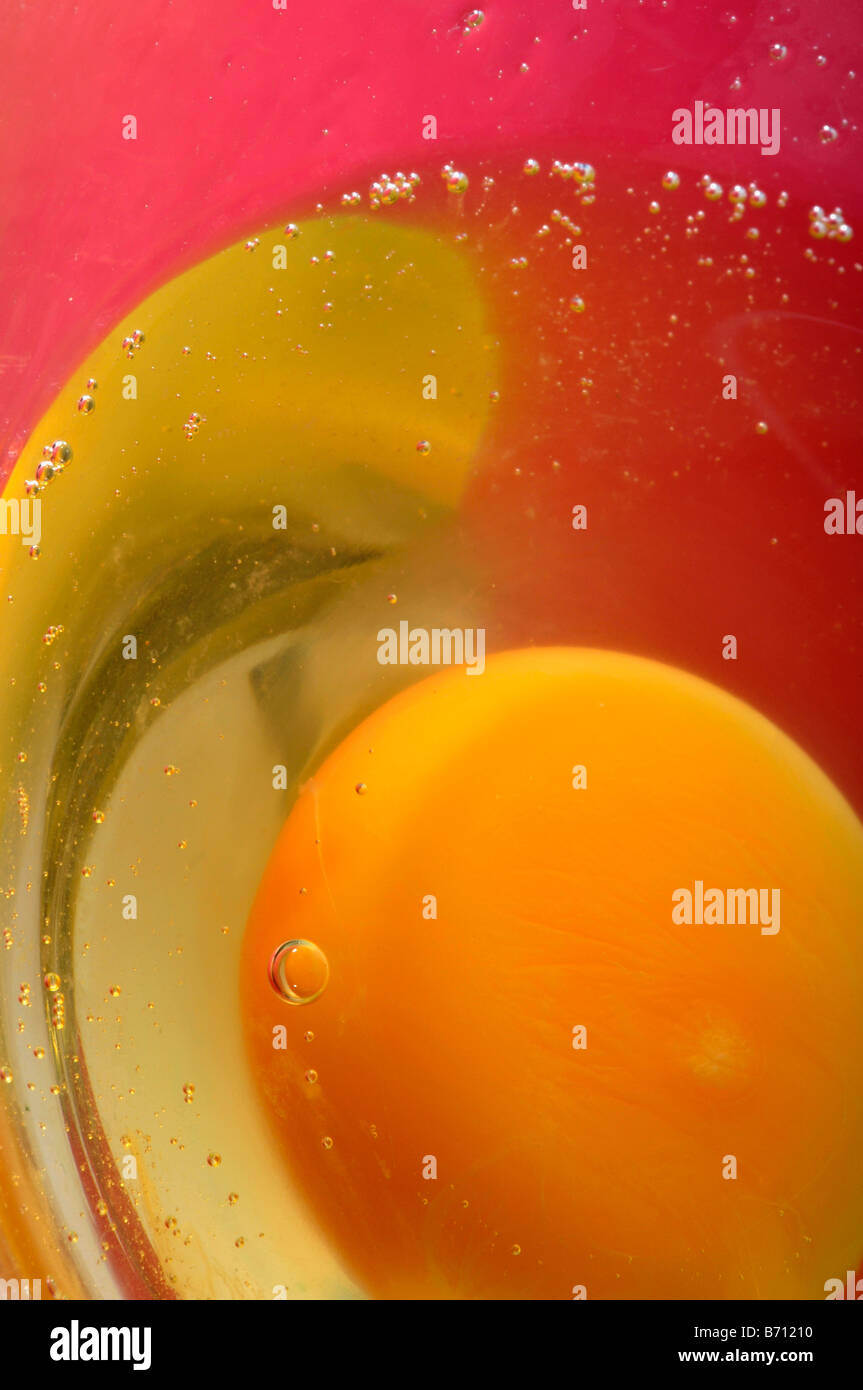 a raw egg in glass yolk yellow white pink orbital - Stock Image