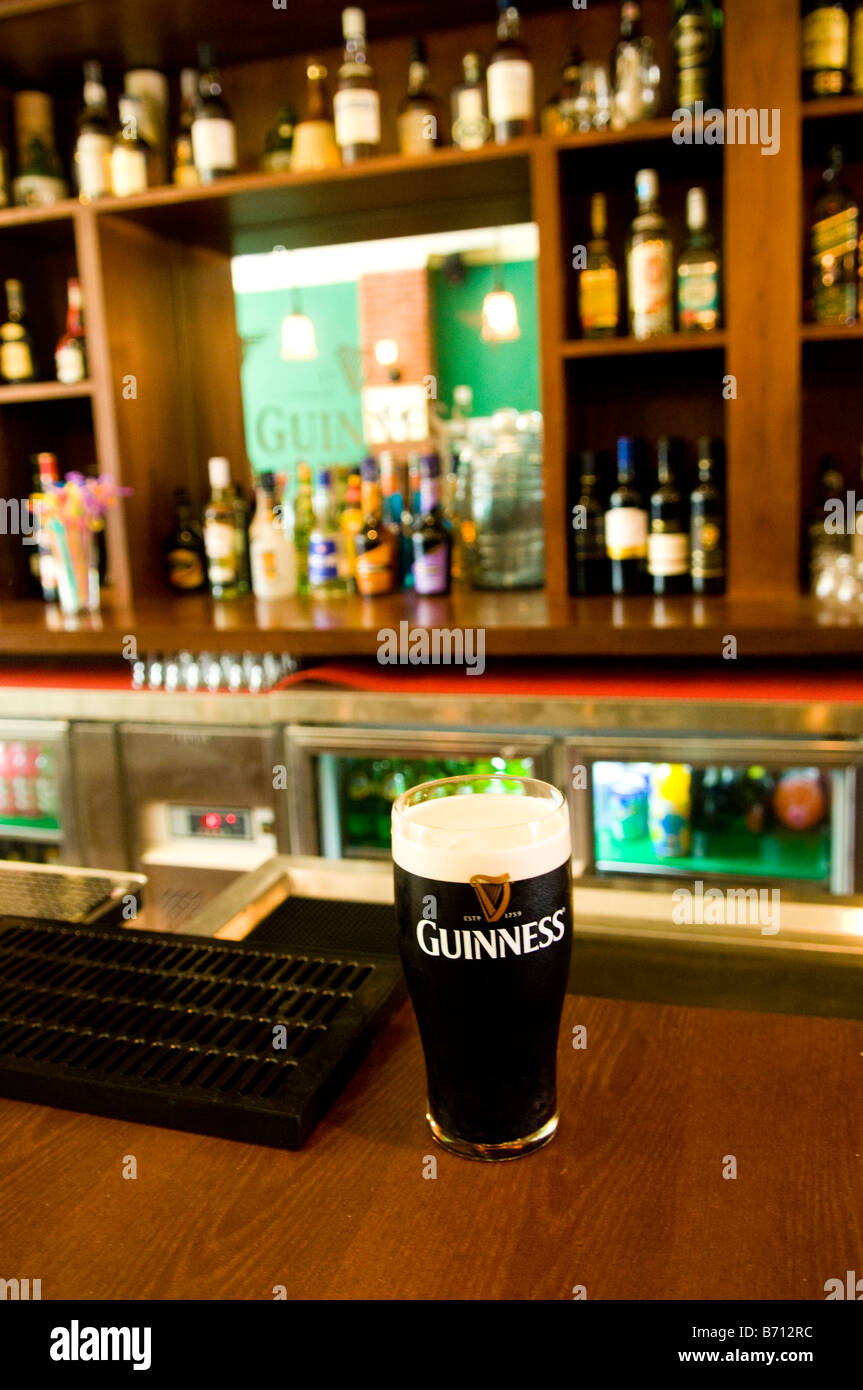 A glass of Guinness beer served in an Irish pub - Stock Image