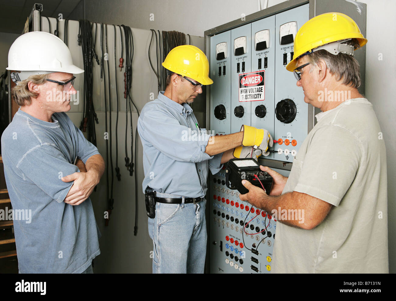 Electricians Working On An Industrial Power Distribution Center While Supervisor Watches All Work Being Performed To Code