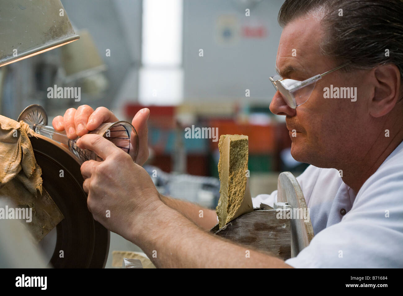 Crystal Cutter: A worker in the crystal factory cuts a precise pattern into a wine glass to make it uniquely Waterford - Stock Image