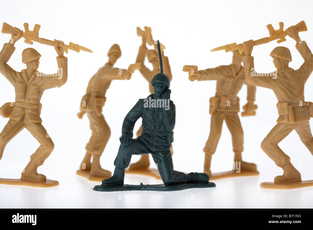 toy soldier radio communication oblivious to being surrounded by enemy soldiers - Stock Image