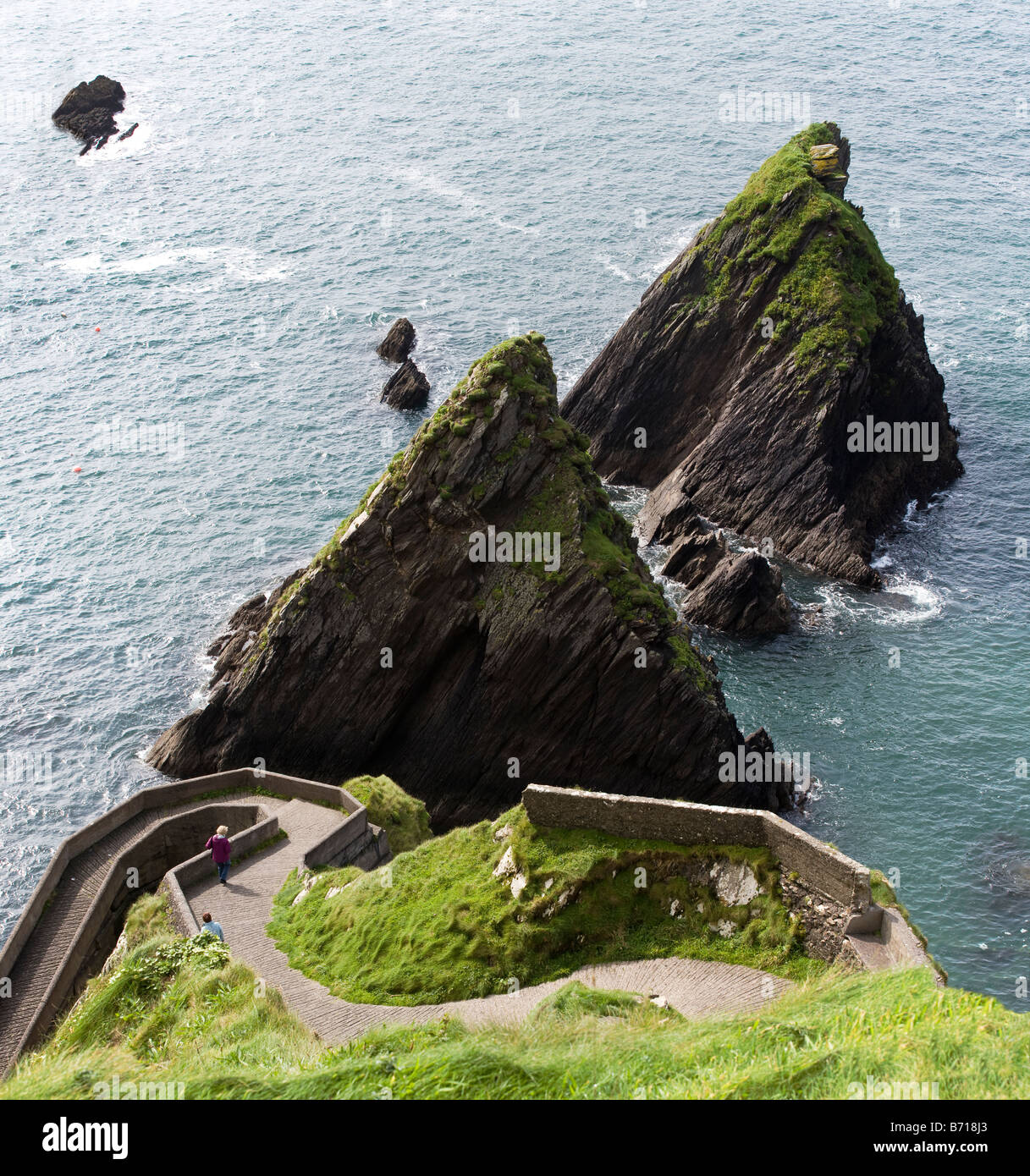 Down to the Water's Edge/ Guarded Ferry landing. Two passengers walk down the path to rock guarded Blasket Island - Stock Image