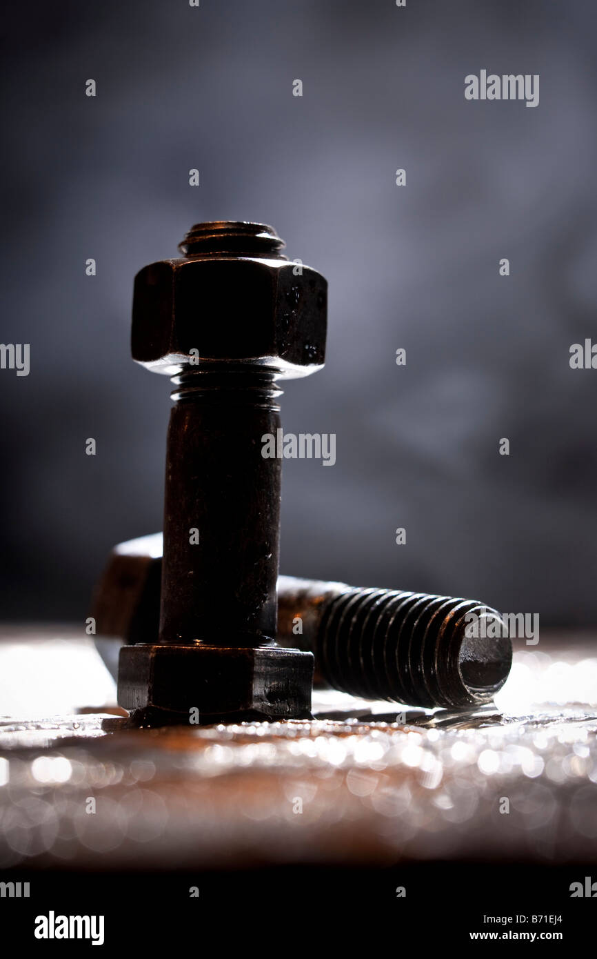 Random artistic pile of threaded bolts and a  hexagonal nut on a sheet steel, backlit. - Stock Image