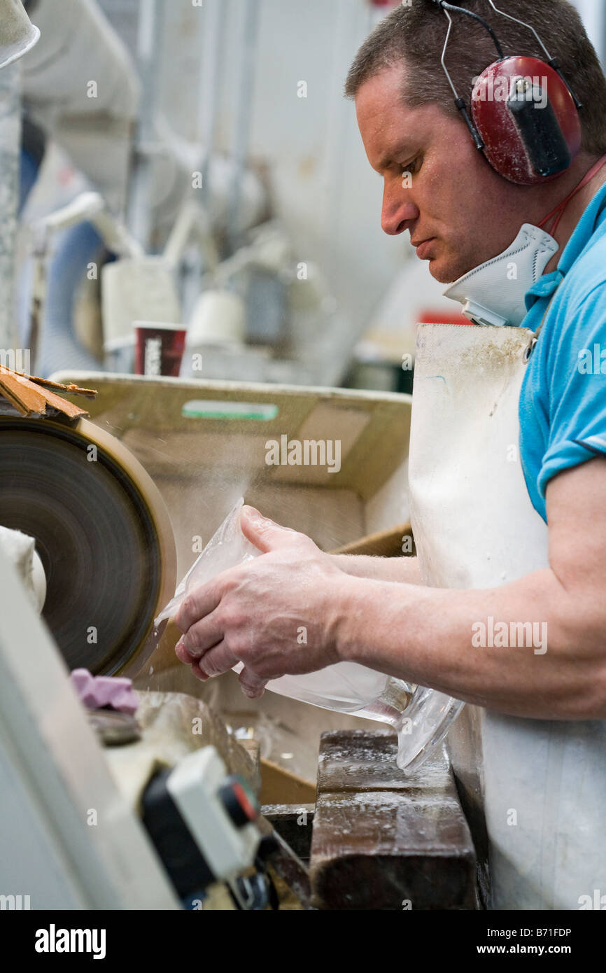 A worker in the crystal factory cuts a precise pattern into a large crystal vase to make it uniquely Waterford - Stock Image
