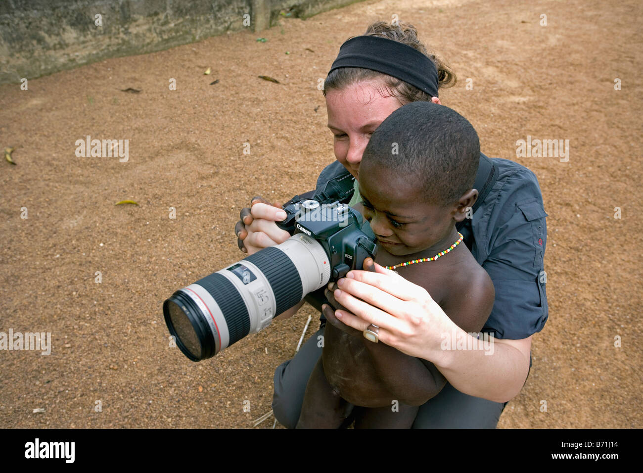 Suriname, Laduani, at the bank of the Boven Suriname river. Woman, tourist, showing camera to boy from Saramaccaner - Stock Image