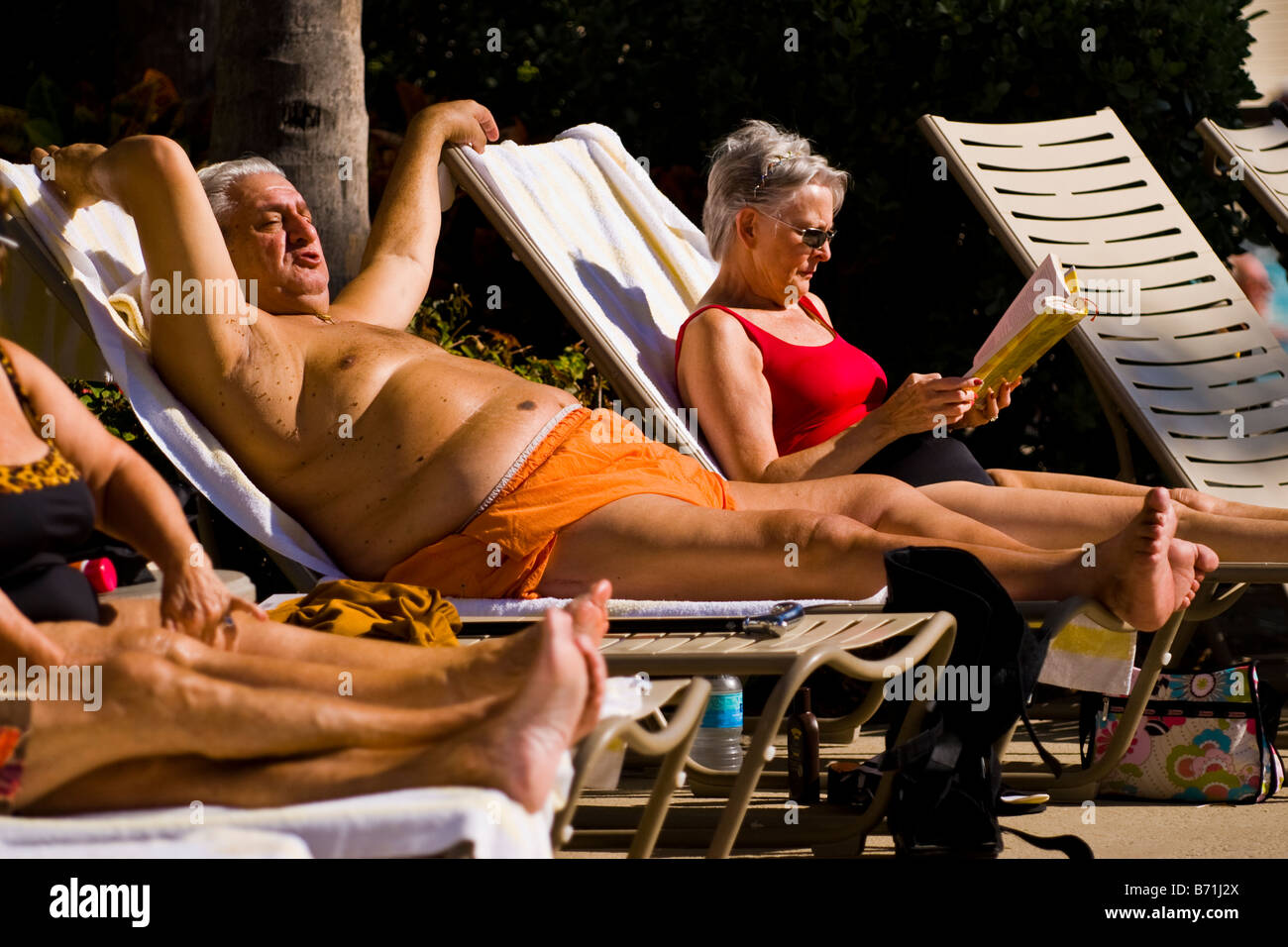 Palm Beach Shores Mature Large Middle Aged Grey Haired Man On Sun Lounger In Orange