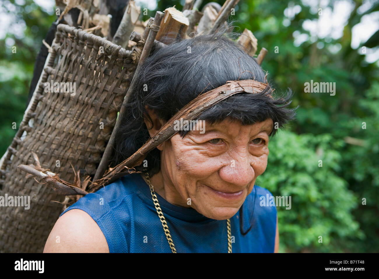 Suriname, Kwamalasamutu, home of indigenous Indians. Akurio Indian man carrying fire wood. - Stock Image