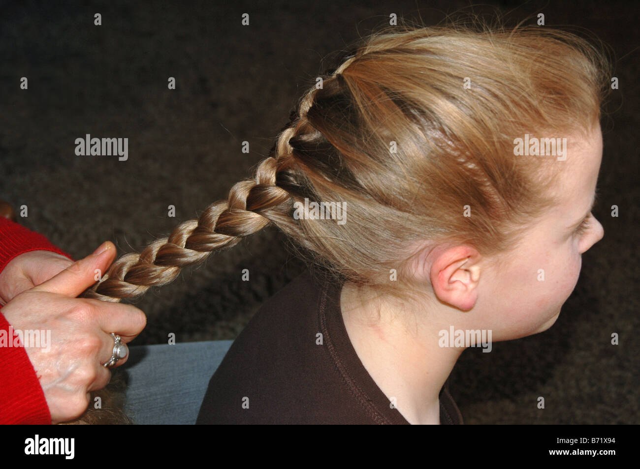 A young girl gets her hair pleated. - Stock Image