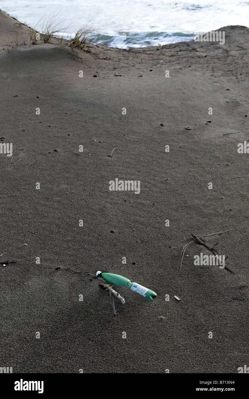 Green Plastic Bottle Washed Up onto Beach - Stock Image