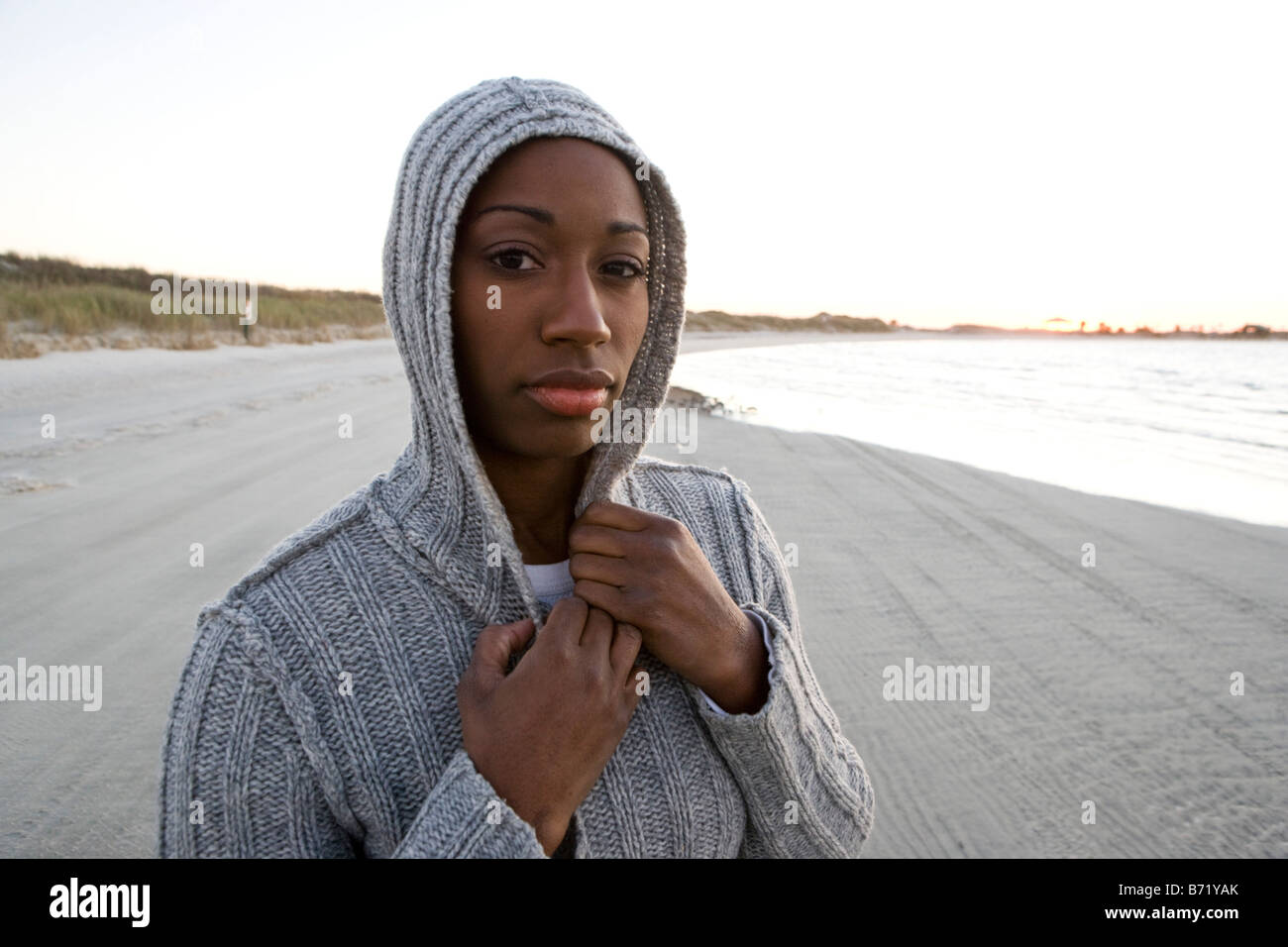 Young African American woman wearing hooded top standing at beach - Stock Image