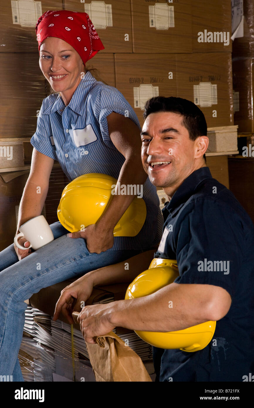 Two workers sitting in storage warehouse - Stock Image