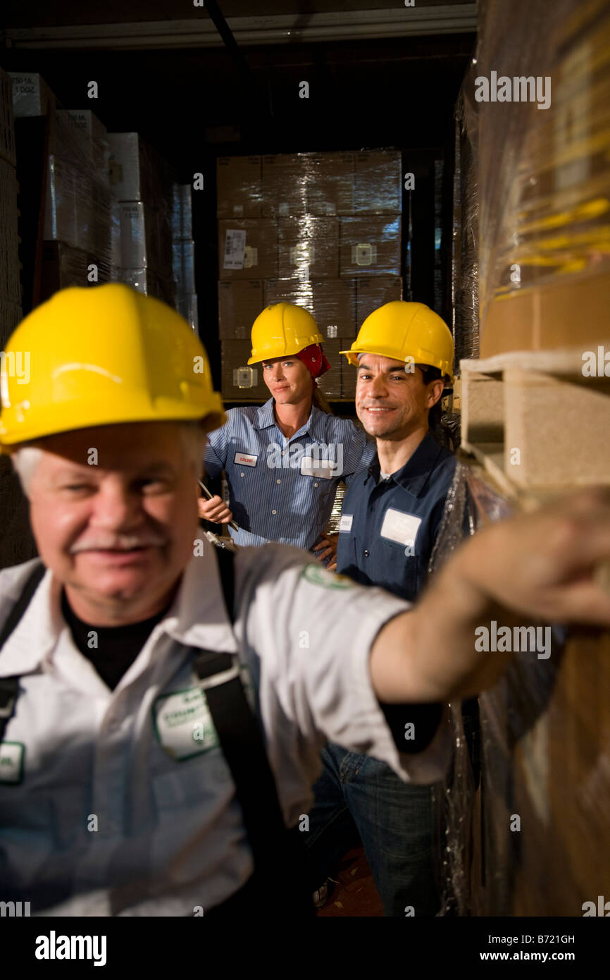 Three co-workers in storage warehouse - Stock Image