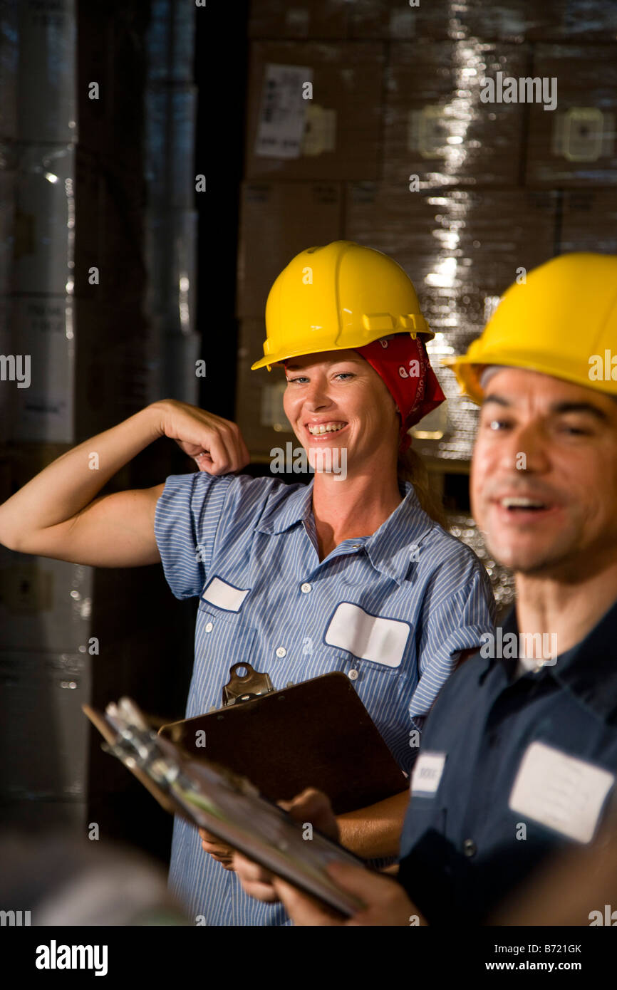Closeup of two co-workers in storage warehouse - Stock Image