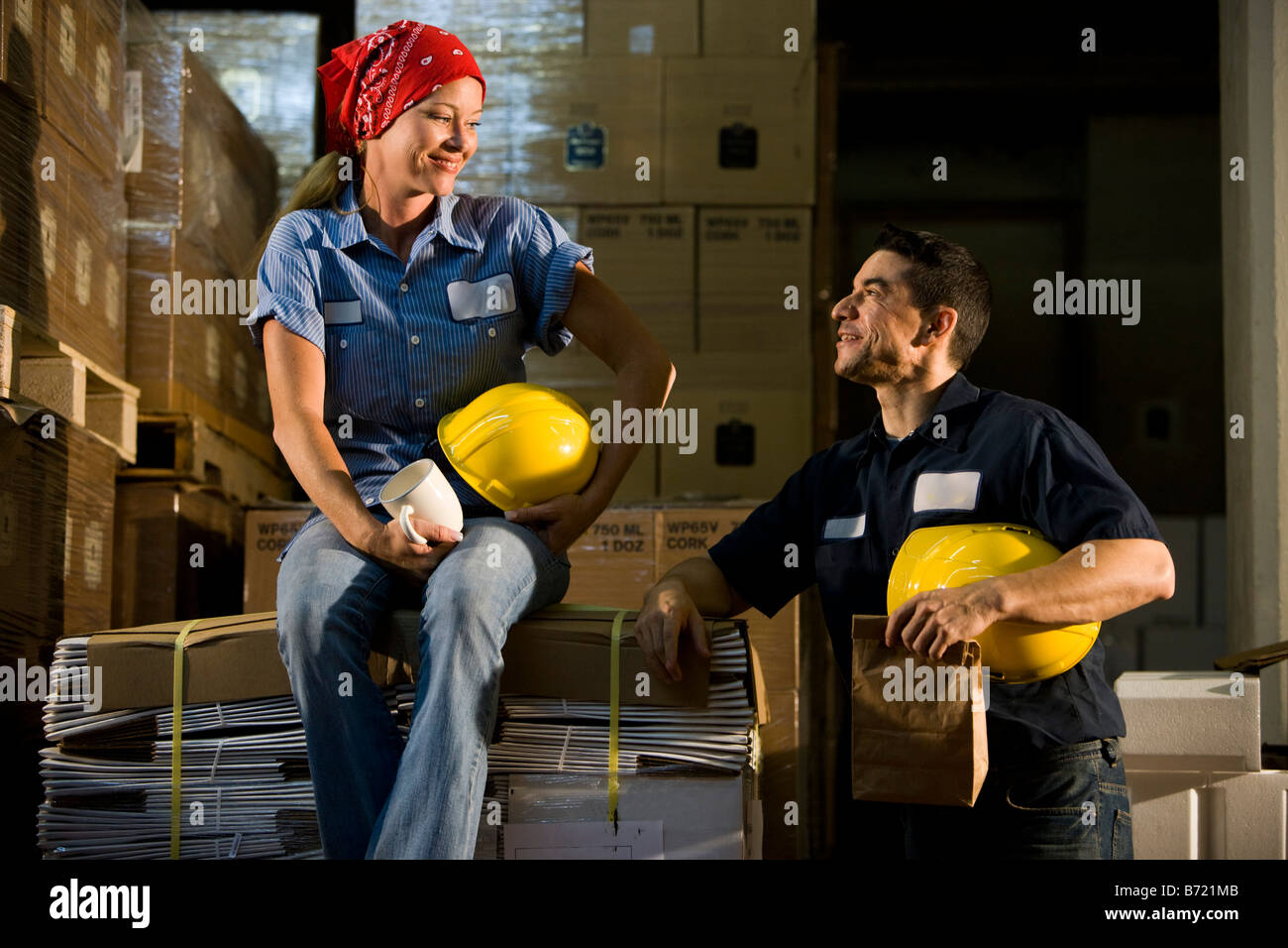 Two co-workers relax in storage warehouse - Stock Image