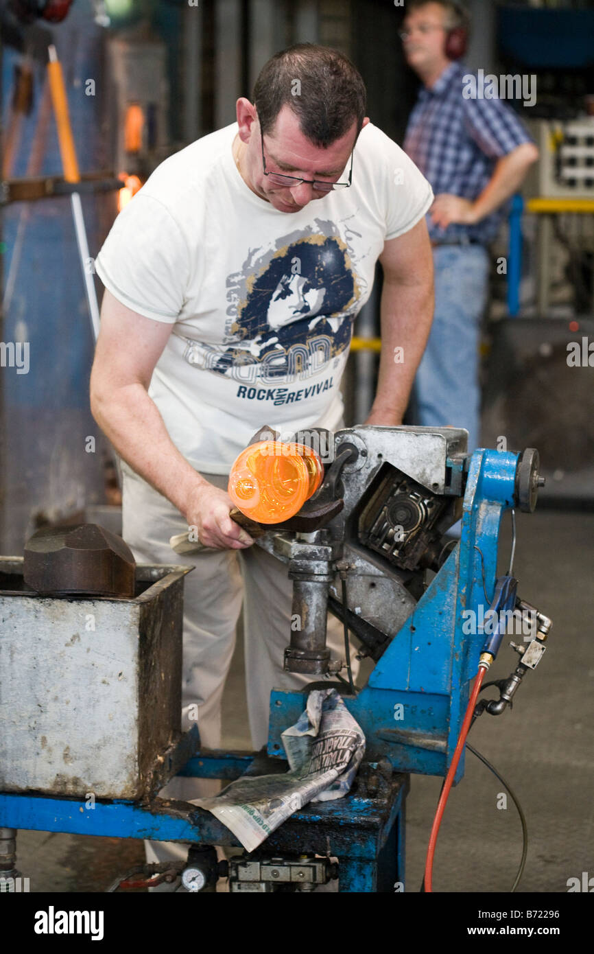 Throwing the Vase: A worker in the crystal factory rotates and shapes a piece of blown crystal glass Stock Photo