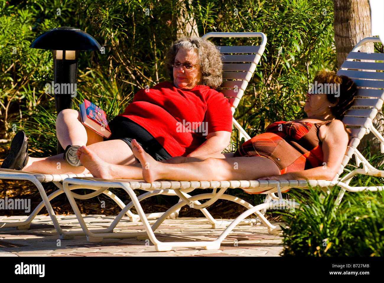 Palm Beach Shores , two middle aged women in sunglasses & bathing costume on sun loungers by pool - Stock Image