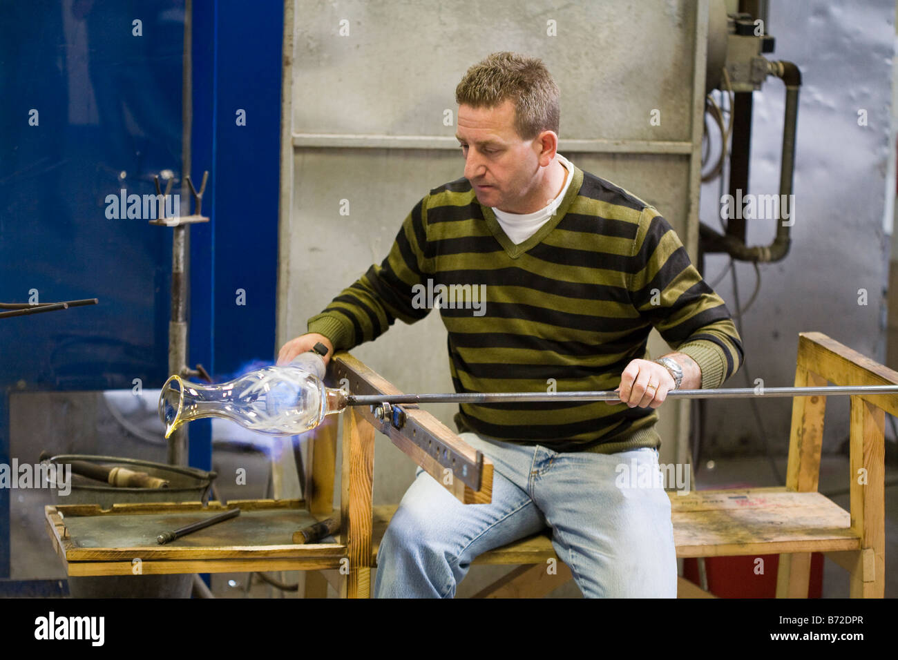 Reheating the Crystal: A worker in the crystal factory rotates and reheats a piece of blown crystal glass using - Stock Image