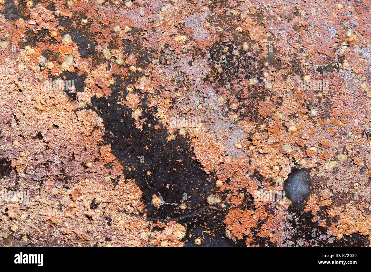 Background abstract texture of rusted metal in shades of orange and brown colors - Stock Image