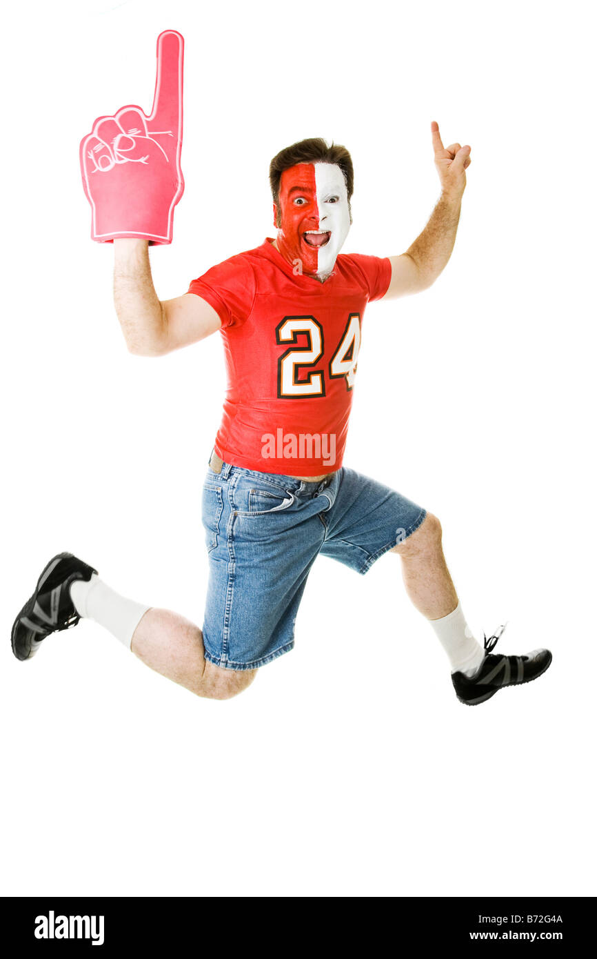 Enthusiastic sports fan jumping for joy over his team s success Full body isolated on white - Stock Image