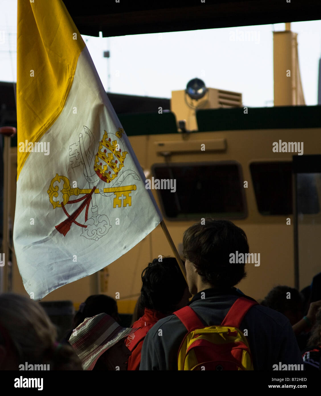 A pilgrim holding the flag of Vatican City the Holy See waits for a ferry at Circular Quay. - Stock Image