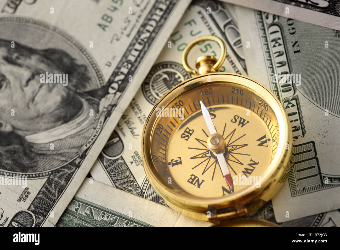 Gold compass on pile of US money - Stock Image