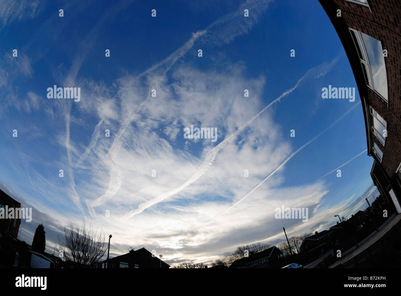 vapor trails or chemtrails from jets in sky - Stock Image