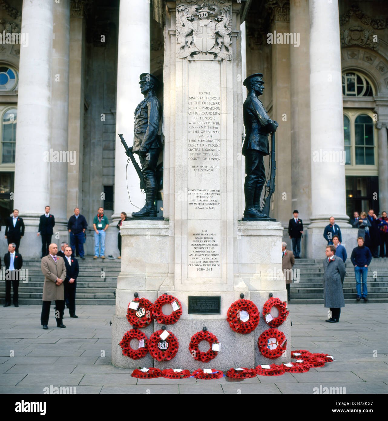 People stand in silence on Remembrance Day Armistice Day outside the Royal Exchange War Memorial London England - Stock Image