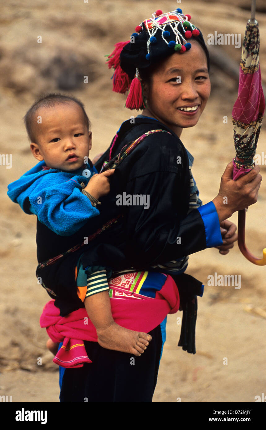 A Hmong Girl Carries a Baby on her Back in the Countryside near Luang Prabang, northern Laos - Stock Image