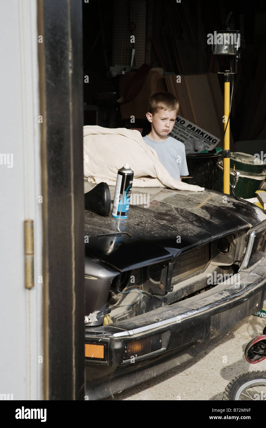 Boy standing behind a car in a garage - Stock Image