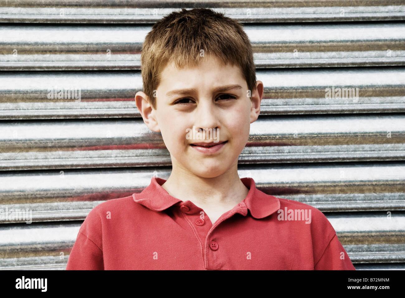 Boy standing in front of garage door - Stock Image