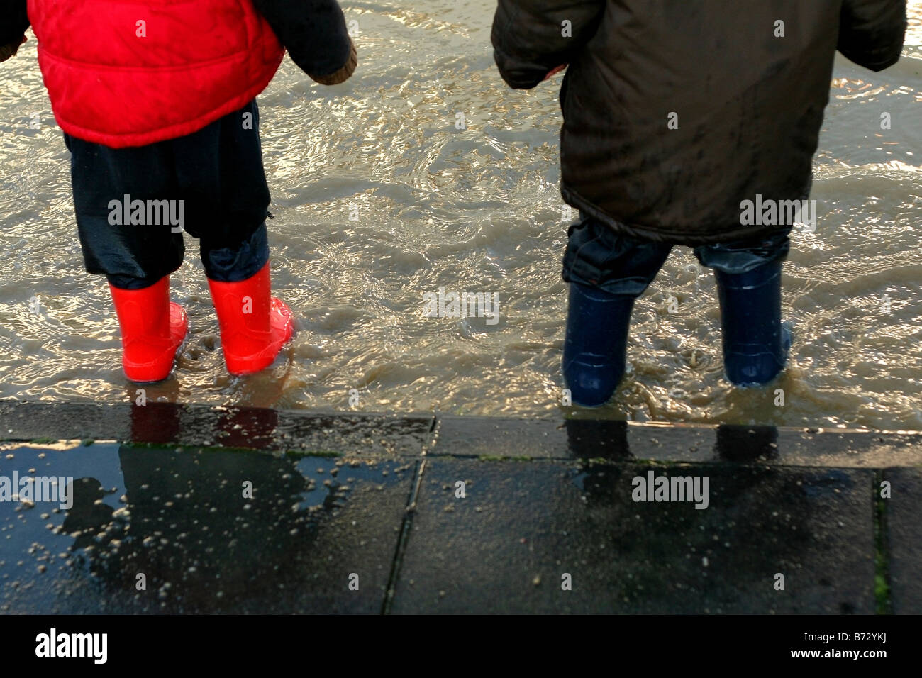 children wearing wellington boots and playing in puddles - Stock Image