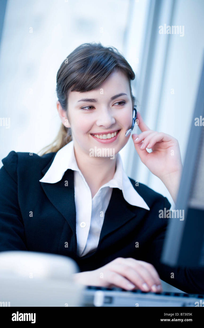 Young woman in formalwear using bluetooth - Stock Image