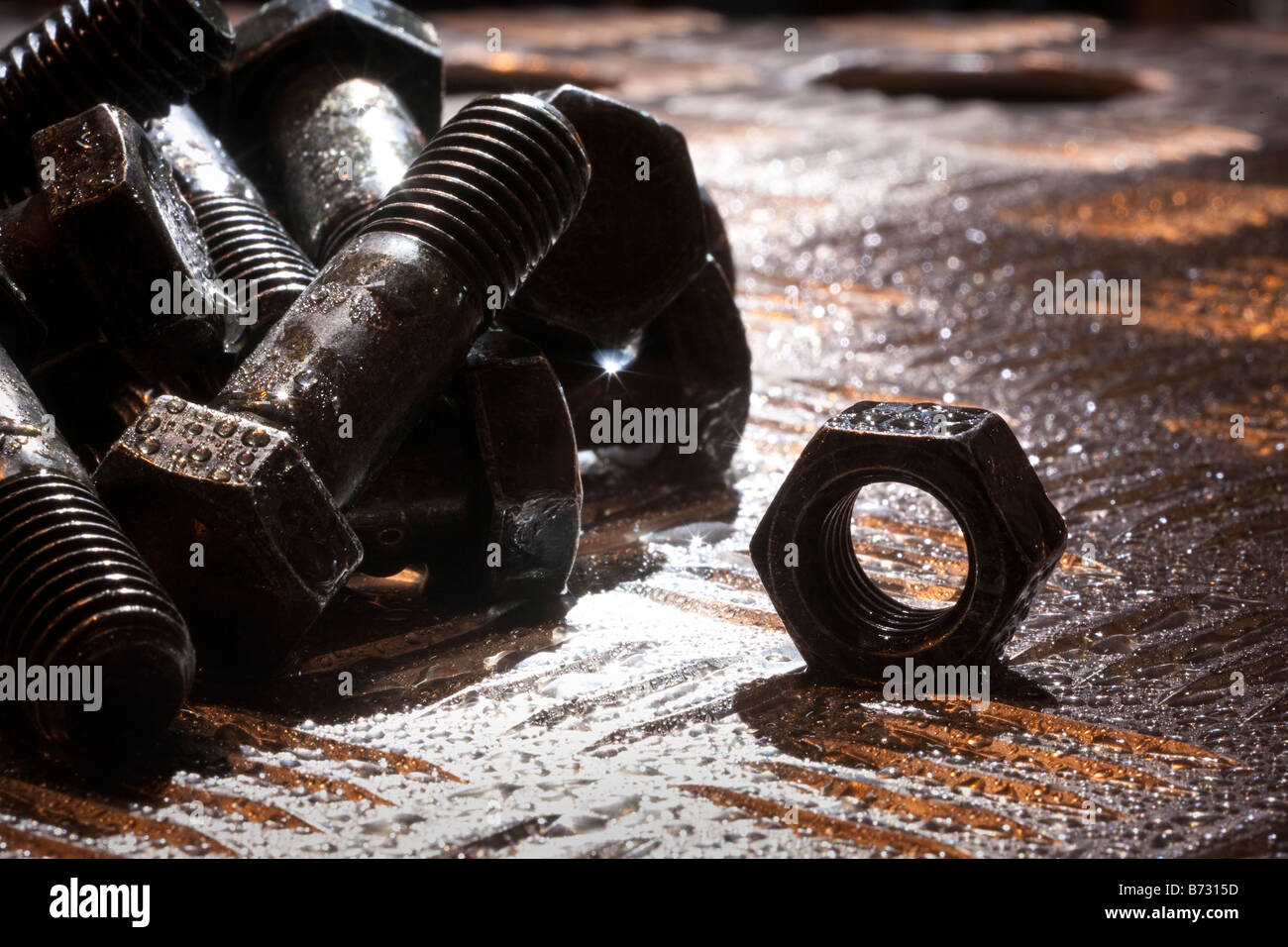 Random artistic pile of threaded bolts and a  hexagonal nut on a sheet steel, backlit, - Stock Image
