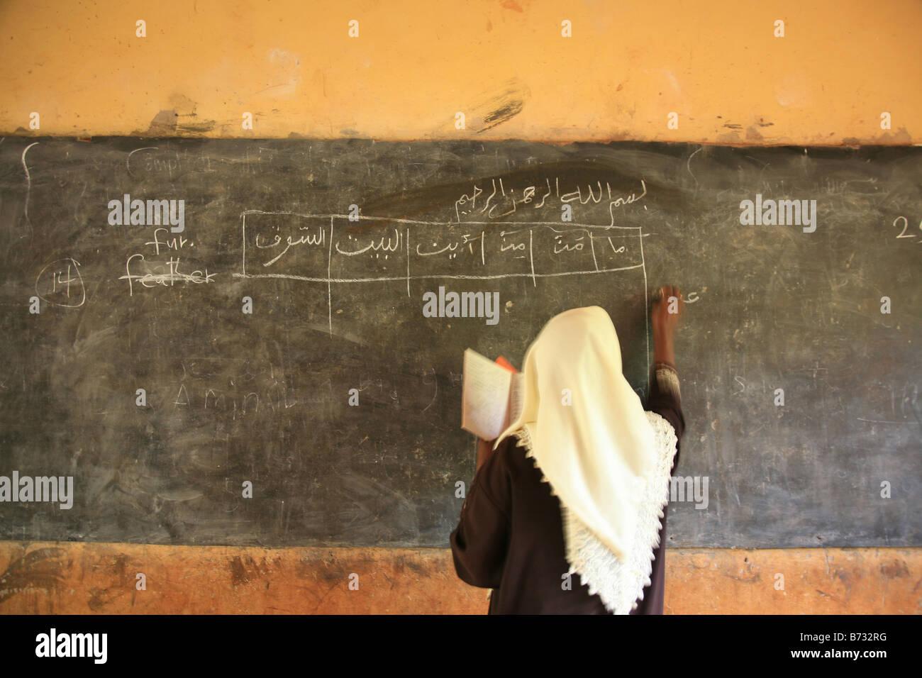 A teacher from the Islamic school in Sunyani Ghana writing arabic sentences on the black board In Ghana coranic - Stock Image