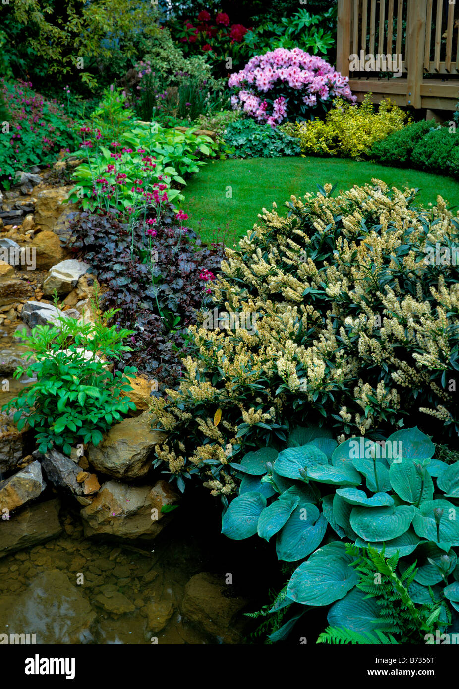 Rockery and Water Garden with mixed border and lawn - Stock Image