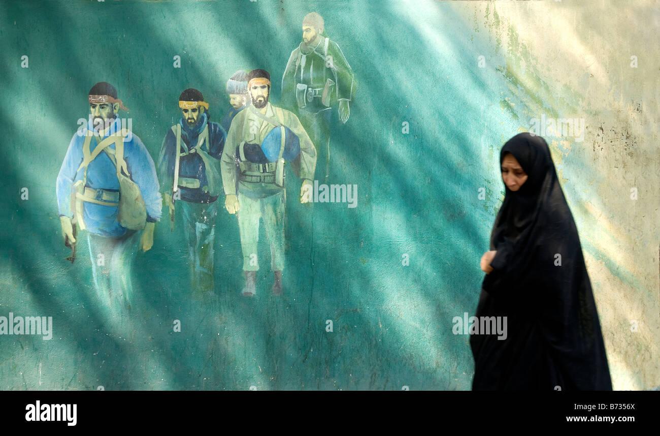 tehran black veil veiled muslim woman walking past anti american martyrs mural by old american embassy in teheran Stock Photo