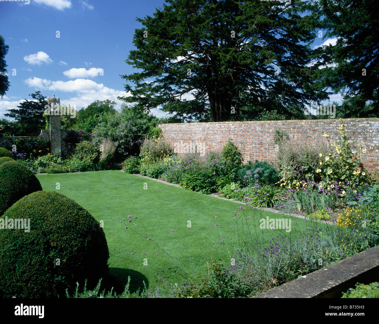 Eagle court in gardens of house Statue of Eagle on wall Lawn Flowers National Trust TINTINHULL HOUSE SOMERSET ENGLAND Stock Photo