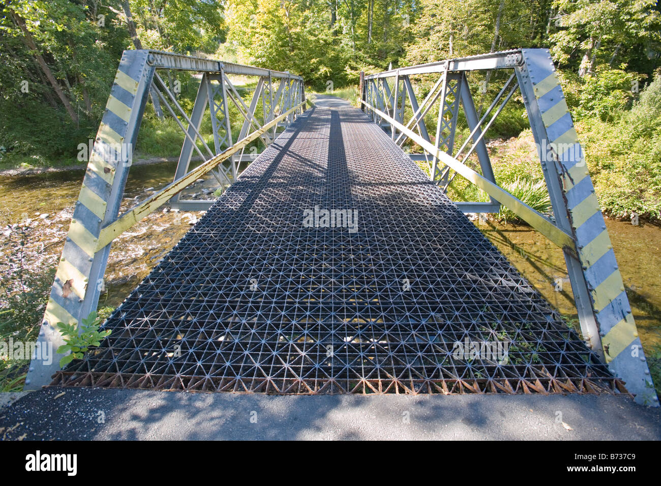 A lonely view of a country metal bridge with a flowing creek underneath the bridge. Stock Photo