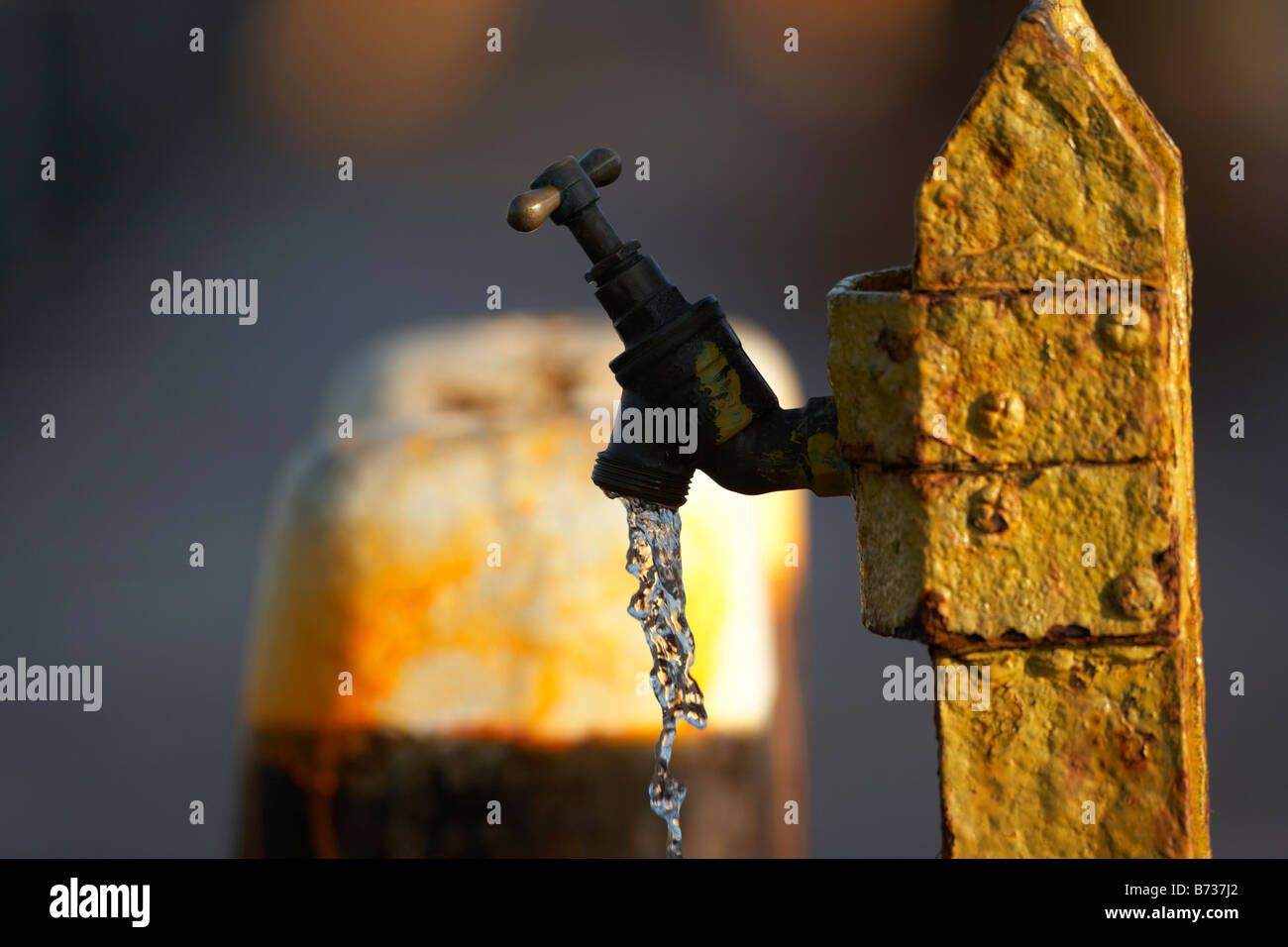 outdoor tap left running with water flowing out freely county down Northern Ireland UK - Stock Image