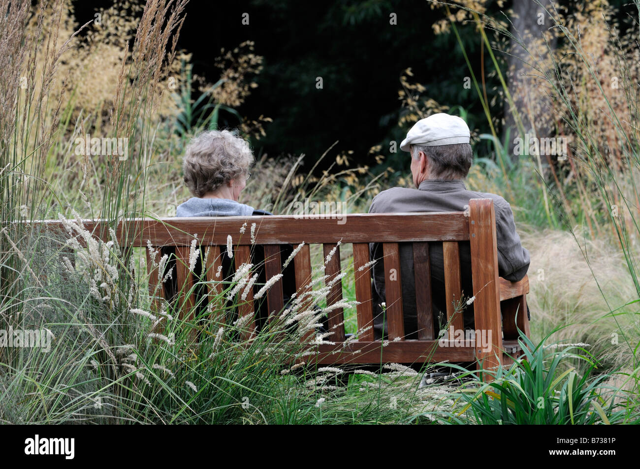 Retired elderly couple man woman sitting viewing looking look view on a bench seat garden watch watching enjoyment Stock Photo