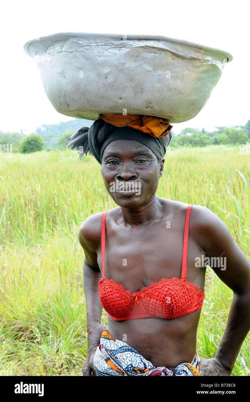 Liberian woman in red top with tin pan balancing on head near Grassfield Nimba County - Stock Image